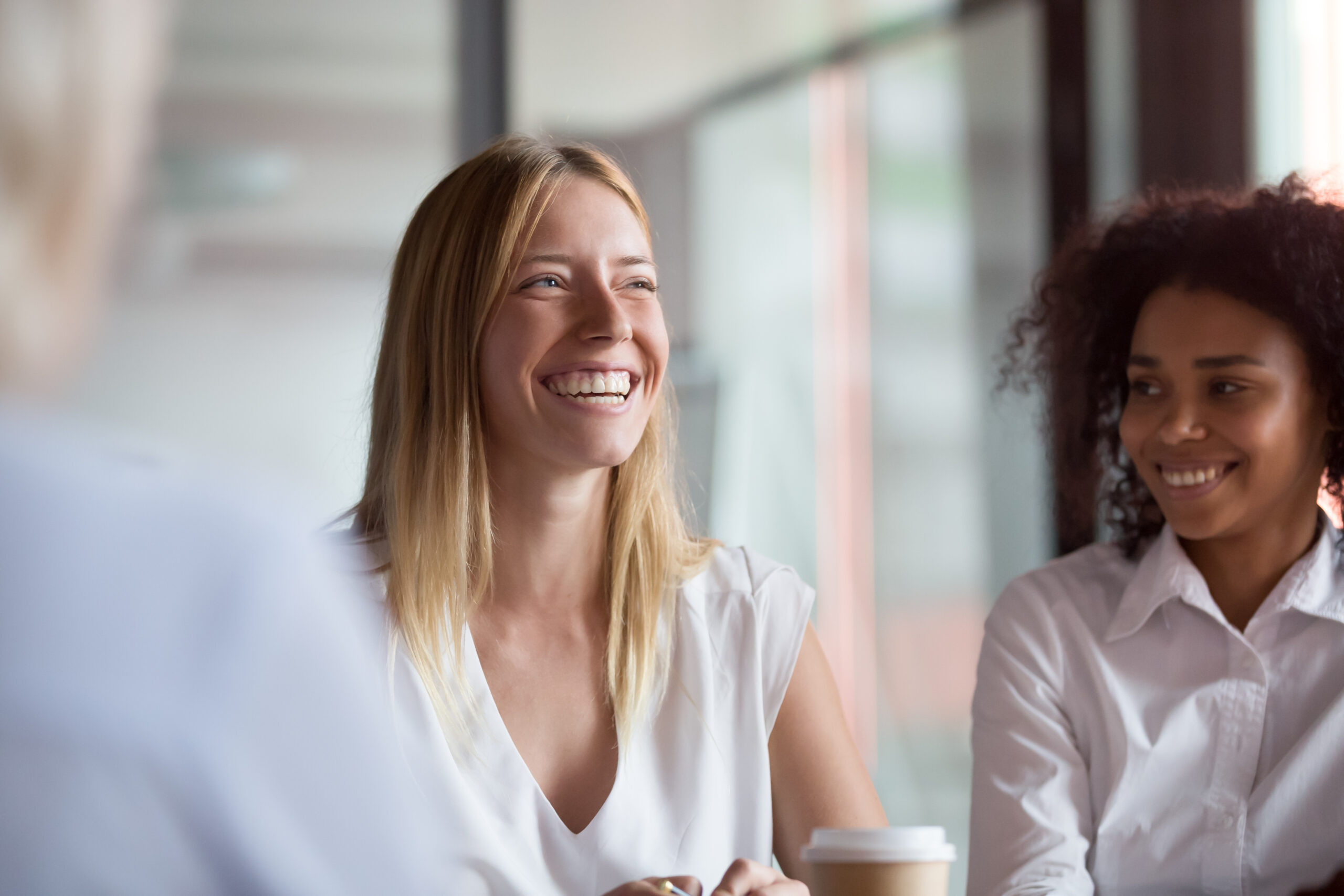 Happy young businesswoman coach mentor leader laughing at group meeting